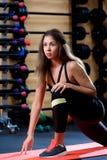 Trevlig kvinna som värmer upp i idrottshallen arkivbild