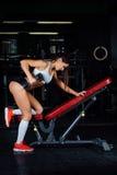 Trevlig kvinnagenomkörare på en bänk med hanteln i idrottshallen Royaltyfri Foto