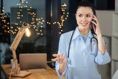 Trevlig kvinnlig doktor som talar på telefonen royaltyfri fotografi