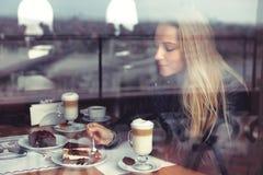 Trevlig kvinnlig i kafé som äter kakan royaltyfri fotografi