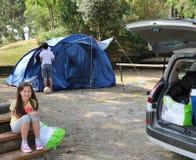 Trevlig liten flicka och hennes broder, medan installera tältet i th Arkivbild