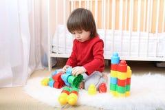 Trevlig litet barnpojke som spelar plast- kvarter Royaltyfri Foto
