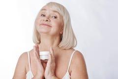 Trevlig lycklig kvinna som använder anti-ålderskönhetsmedel royaltyfria bilder
