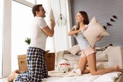 Trevlig lycklig man och kvinna som har en kuddekamp arkivfoton