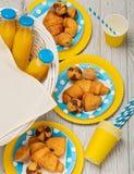 Trevlig ny mat och korg på gräset Söt picknick - orange fruktsaft och muffin som är croissan arkivfoton