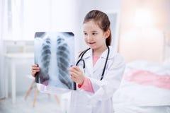 Trevlig positiv flicka som studerar röntgenfotografering fotografering för bildbyråer