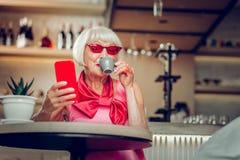 Trevlig positiv hög kvinna som tycker om hennes kaffe royaltyfria bilder
