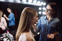 Trevlig positiv makeupkonstnär som använder framsidapulver Royaltyfria Foton