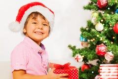 Trevlig pys i jultomtenhatt med närvarande le Arkivfoto