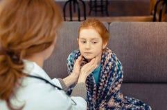 Trevlig röd haired flicka som har hennes hals att kontrolleras royaltyfri fotografi