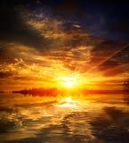 Trevlig röd solnedgång över sjövatten Arkivbild