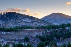 Trevlig sikt av bergen i solnedgångljuset royaltyfria foton