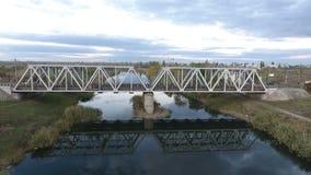Trevlig sikt från höjden på järnvägbron som skjuter ett surr som flyger över floden med en sikt av järnvägen arkivfilmer