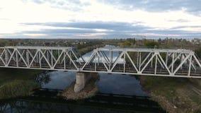 Trevlig sikt från höjden på järnvägbron som skjuter ett surr som flyger över floden med en sikt av järnvägen stock video