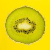 Trevlig skiva av kiwin som täckas med bubblor på guling Fotografering för Bildbyråer