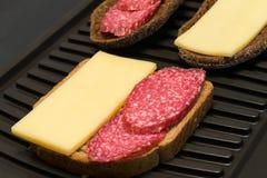 Trevlig smörgås med korven och ost på rostat brödbakgrund Arkivfoto