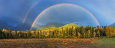 Trevlig sommarregnbåge över bergen Förbluffa regnig och molnig dag Kanadensare Rocky Mountains, Kanada fotografering för bildbyråer
