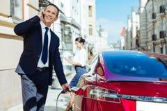Trevlig stilig affärsman som tankar hans bil Fotografering för Bildbyråer