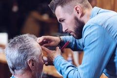 Trevlig stilig barberare som gör en frisyr royaltyfria bilder