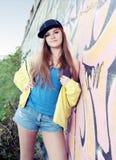 Trevlig tonåring för ung kvinna nära den stads- väggen Royaltyfri Fotografi