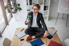 Trevlig ung affärsmansi i lotusblomma poserar på tabellen i rum Han dricker kaffe och blick på fönstret Manstillhet och fridsamt arkivbilder