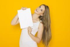 Trevlig ung attraktiv kvinna som rymmer tomt papper Arkivbild