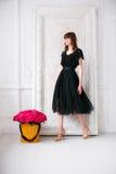 Trevlig ung blond flicka i en svart klänning och skor på höga häl att lukta blommar den hållande purpurfärgade rosbuketten i hatt Royaltyfri Bild