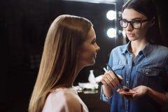 Trevlig ung visagiste som sätter på makeup Fotografering för Bildbyråer