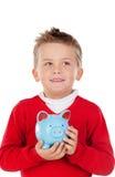 Trevlig unge med blå moneybox Fotografering för Bildbyråer
