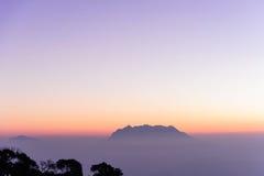 Trevlig vit dimma på berget i morgonen med soluppgångljus och trädkontur och litet berg i bakgrund Royaltyfri Fotografi
