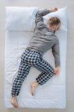 Trevlig vuxen man som sover på hans buk Royaltyfria Bilder