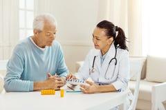 Trevlig yrkesmässig doktor som rymmer en ask med preventivpillerar royaltyfri bild
