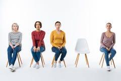 Trevliga allvarliga kvinnor som sitter på stolarna Arkivfoton