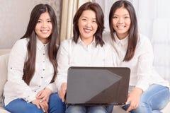 Trevliga asiatiska flickor som sitter på bärbara datorn arkivbild