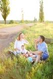 Trevliga föräldrar som sitter på gräs med det lilla barnet och blåser bubblor arkivbild