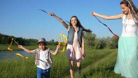 Trevliga flickor med pysen hoppar med kulöra band i hand utomhus längs sjön lager videofilmer