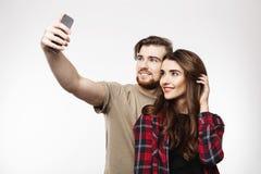 Trevliga gladlynta par som tar selfie på telefonen som ser lycklig royaltyfria foton