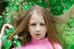 Trevliga liten flickakostnader nära ett träd Arkivfoton