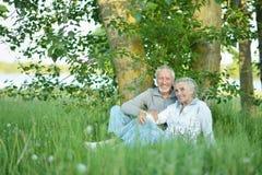 Trevliga mogna par som sitter p? gr?nt gr?s arkivbilder