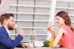 Trevliga par som dricker vitt vin i kafé Royaltyfria Bilder