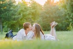 Trevliga par som kysser på ett gräs, ögon stängde sig arkivbild
