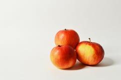 Trevliga saftiga röda äpplen på ljus bakgrund Arkivfoton