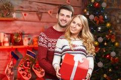 Trevliga stilfulla älska par near julgranen fotografering för bildbyråer