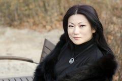 Trevliga unga asiatiska kvinnor som sitter på en bänk. Arkivfoton