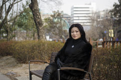 Trevliga unga asiatiska kvinnor som sitter på en bänk. Arkivbild