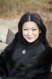 Trevliga unga asiatiska kvinnor som sitter på en bänk. Arkivbilder