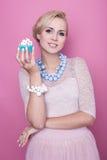 Trevliga unga kvinnor rymmer den lilla färgrika kakan soft för fält för färgpildjup grund Fotografering för Bildbyråer