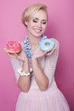 Trevliga unga kvinnor rymmer färgrika donuts soft för fält för färgpildjup grund Arkivfoton