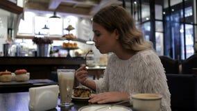 Trevligt äta för flicka som är smaskigt på kafét arkivfilmer