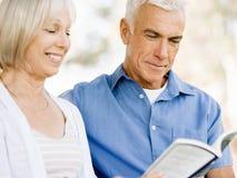 Trevligt åldringparsammanträde utomhus med boken Fotografering för Bildbyråer